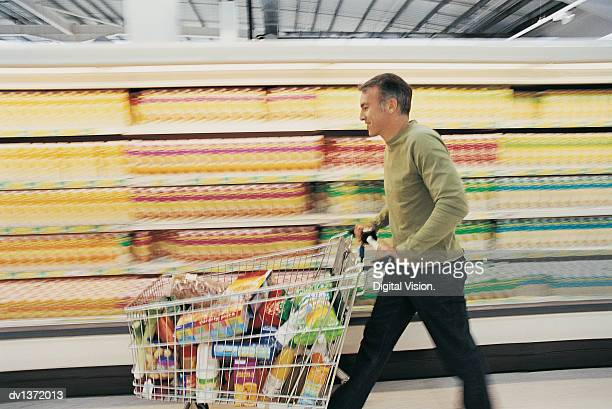 Man Pushing a Shopping Trolley Quickly Down a Supermarket Aisle