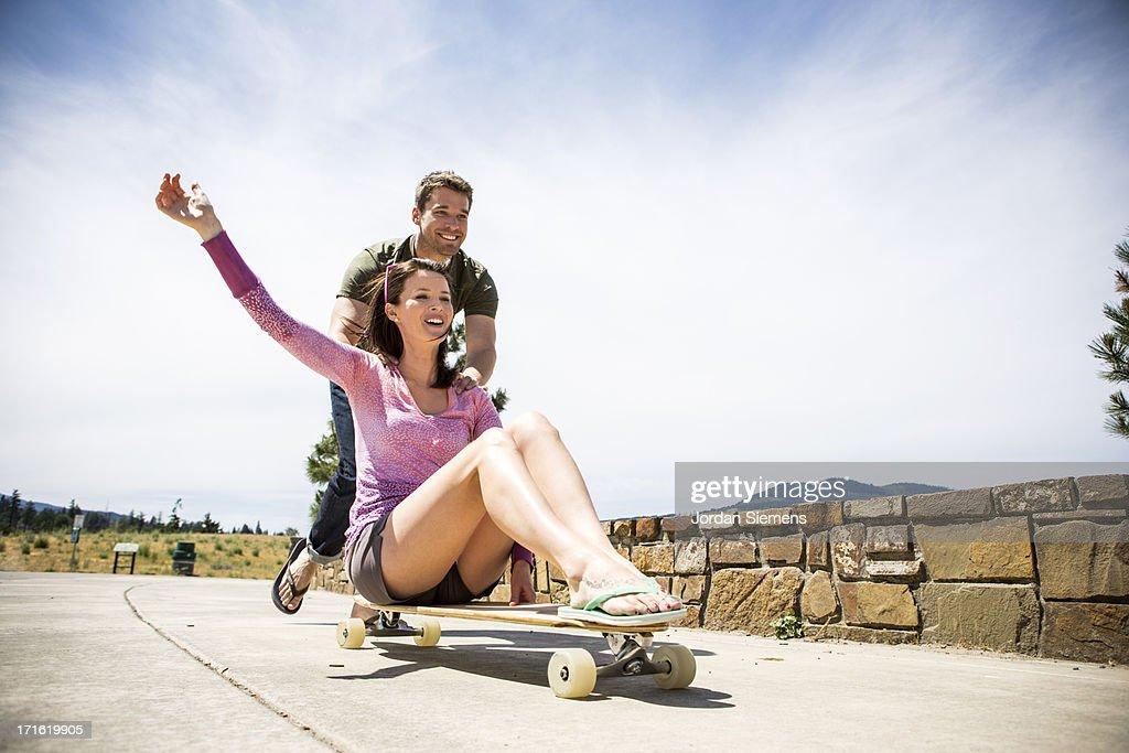 A man pushing a woman on a skateboard.