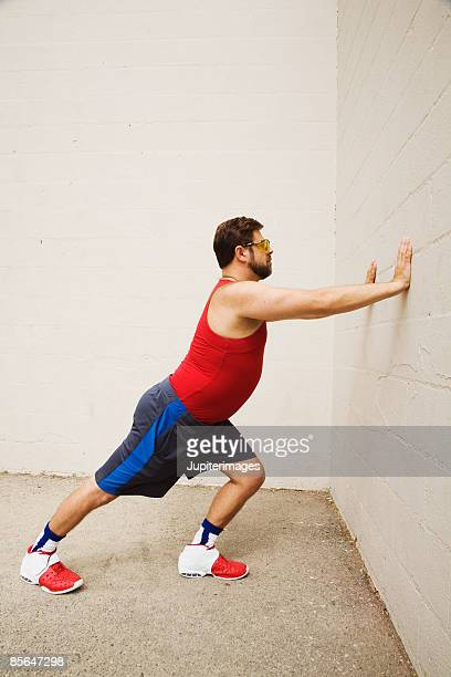 Man pushing against wall