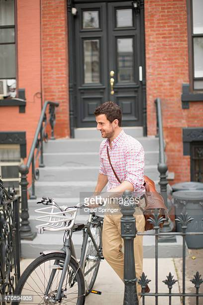 Man pushing bicycle out of front gate