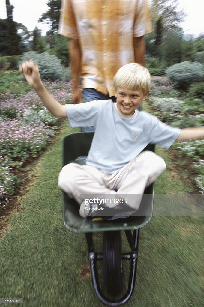 Man pushing boy (12-13) in wheel barrow in garden : Stock Photo