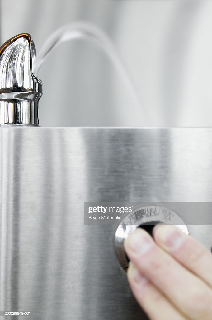 Man pushing button on drinking fountain, close-up of fountain