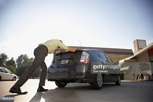 Homme pousser voiture à la station-service