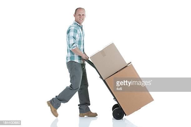 Man pushing cardboard boxes on a sack barrow