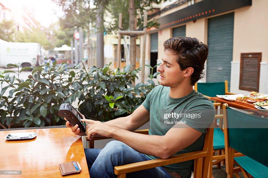 Man pushing creditcard PIN at outside cafe