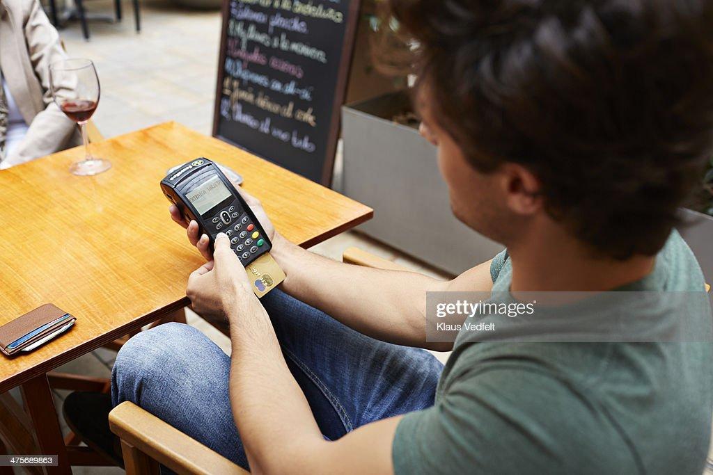 Man pushing creditcard PIN at outside restaurant