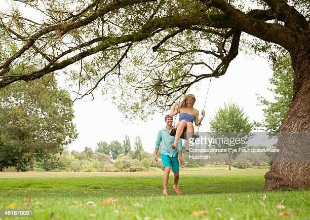 Man pushing girlfriend on swing in park