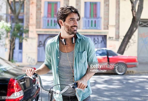 man pushing his bicycle, wearing headphones