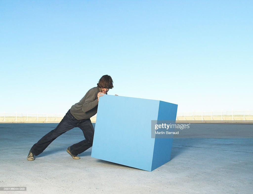 Man pushing large block, outdoors : Stock Photo