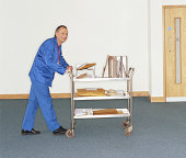 Man pushing mail trolley in office, smiling