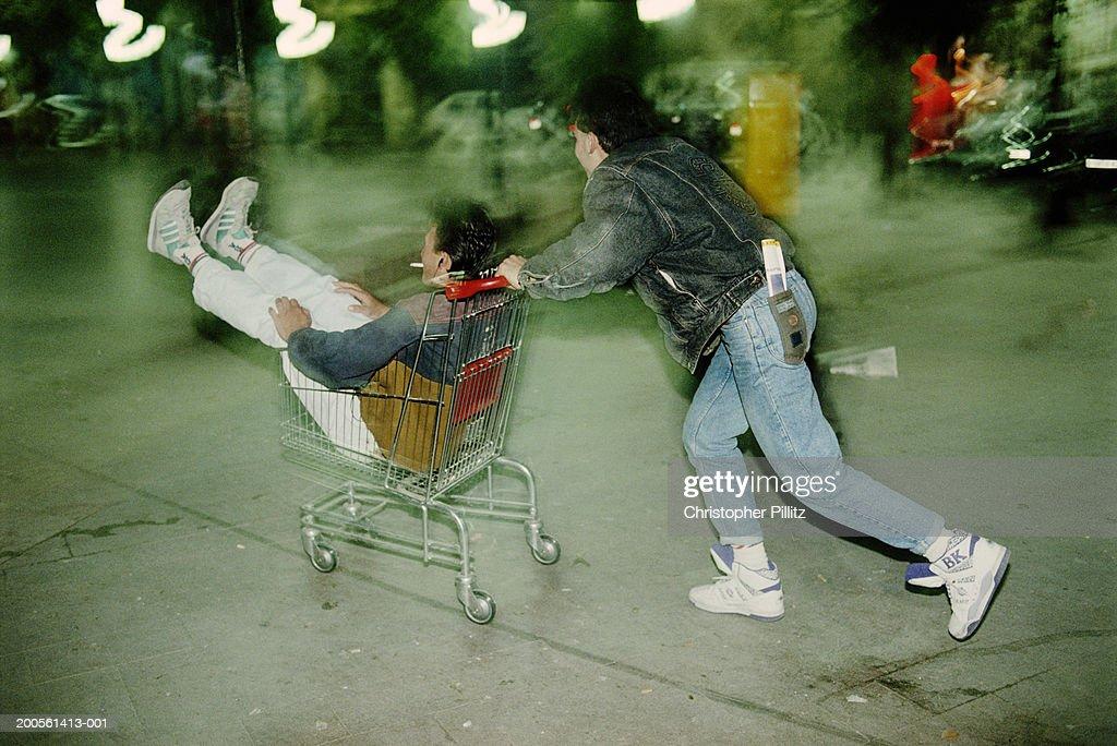 Man pushing man in shopping cart, blurred motion : Stock Photo