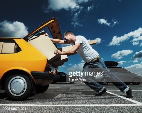 Man pushing packages into open boot of car