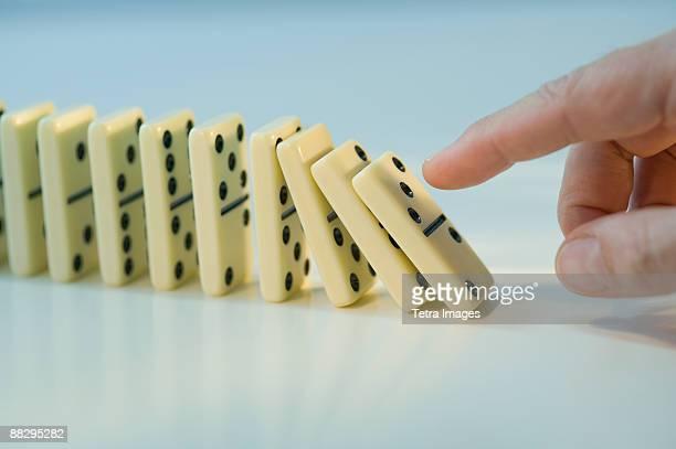 Man pushing row of dominoes
