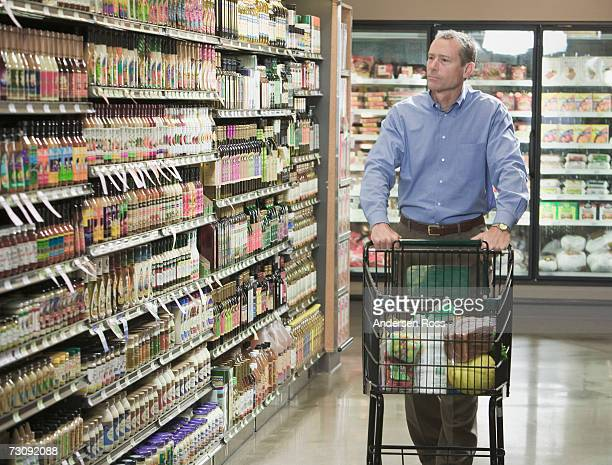 Man pushing shopping trolley in store aisle