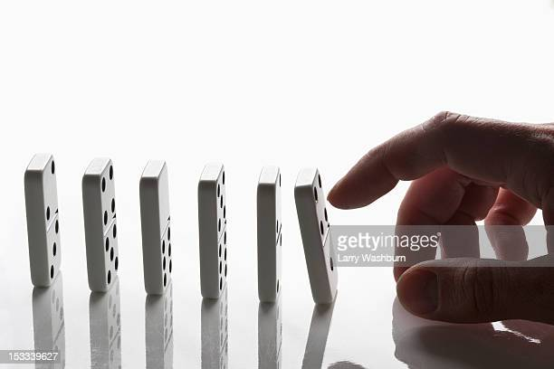 A man pushing the first domino in a row, focus on hand