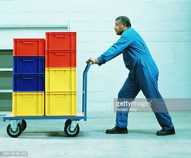 Man pushing trolley of coloured plastic boxes, side view