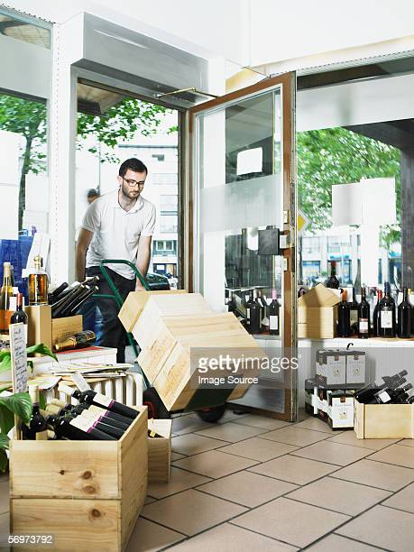 Man pushing trolley of wine boxes into shop