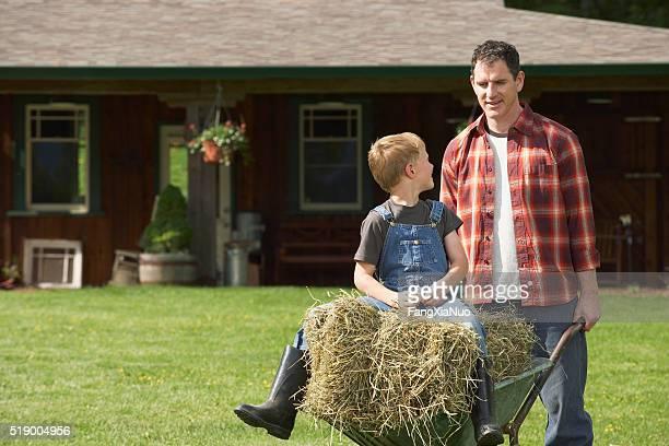 Man pushing wheelbarrow on farm