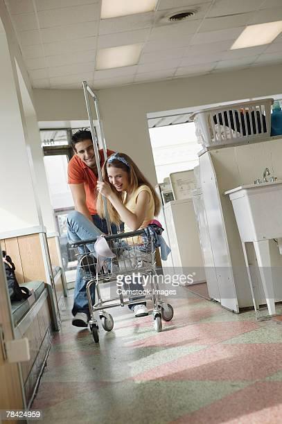 Man pushing woman in cart at laundry facility