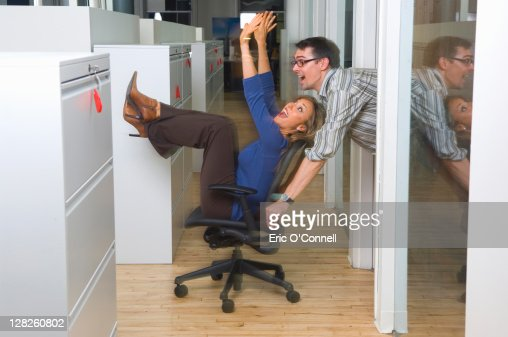 Man pushing woman in chair in a business office : Stock Photo