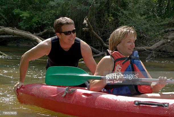 Man pushing woman in kayak away from broken tree branches