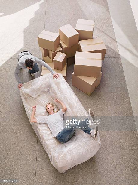 Man pushing woman on sofa in new house