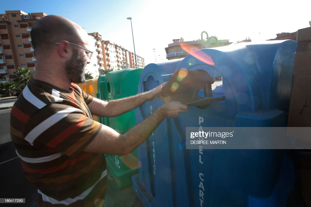 A man puts a cardboard on a recycling container in Santa Cruz de Tenerife on January 30, 2013 .