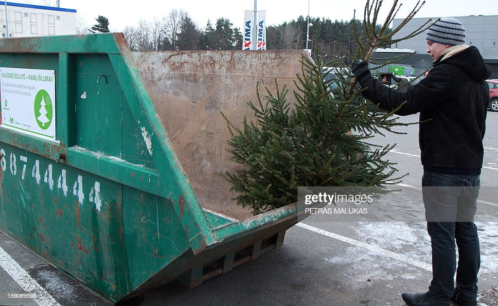 "A man puts a Christmas Tree into a special container in Vilnius, Lithuania on January 7, 2013. The inscription on the container ""Christmas trees - home heating! Here you can bring Christmas trees to be recycled into biofuel"". Having brought joy to Lithuanian families over the holidays, Christmas trees will now warm them through the rest of winter after being converted into biofuel."