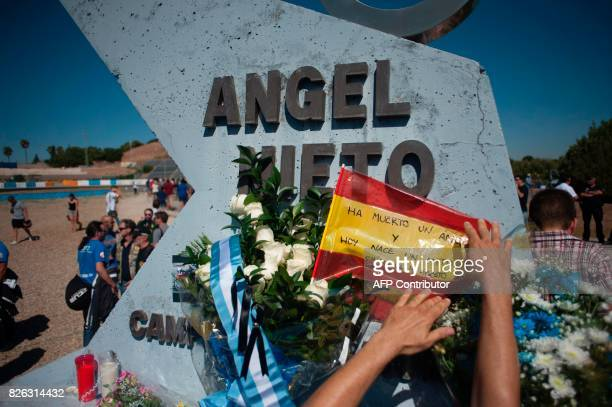 A man puts a flag with the legend 'An angel has died and today a myth is born' on a tribute monument to Spanish former motorcyclist Angel Nieto...
