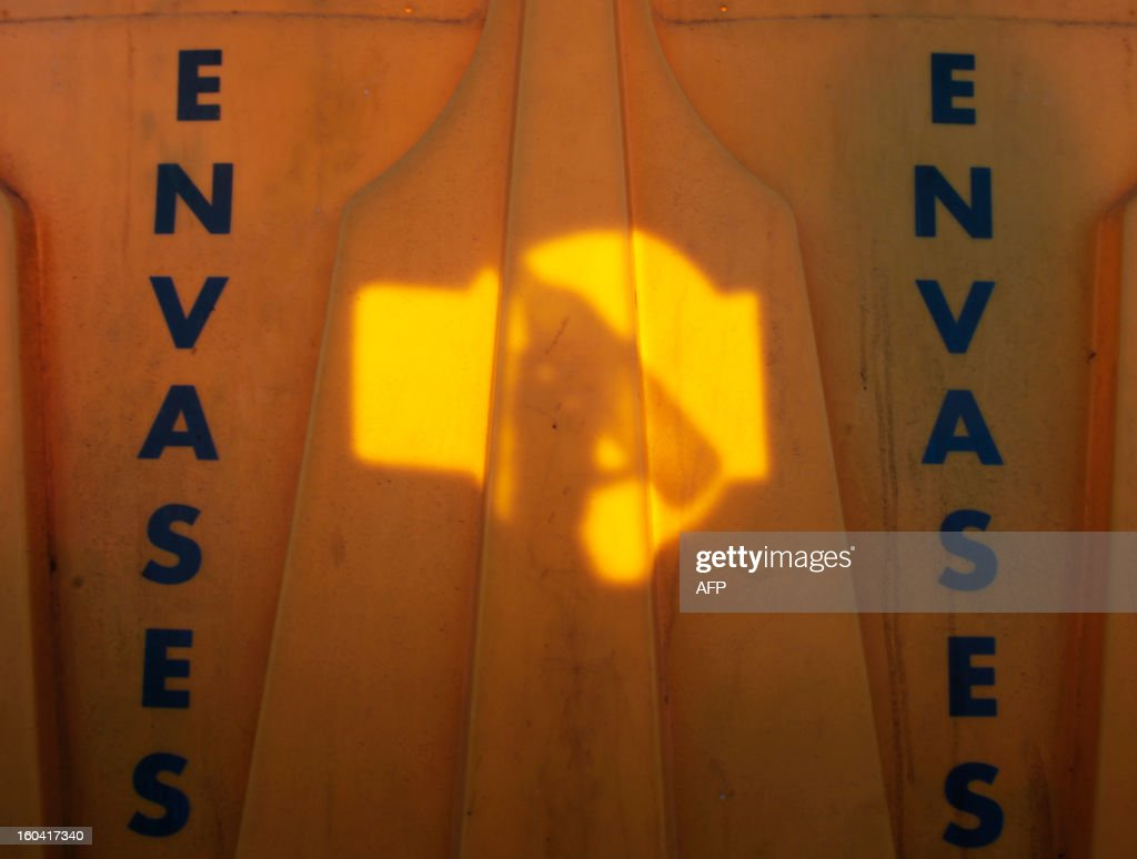A man puts a plastic bottle inside a recycling container in Santa Cruz de Tenerife on January 30, 2013 .