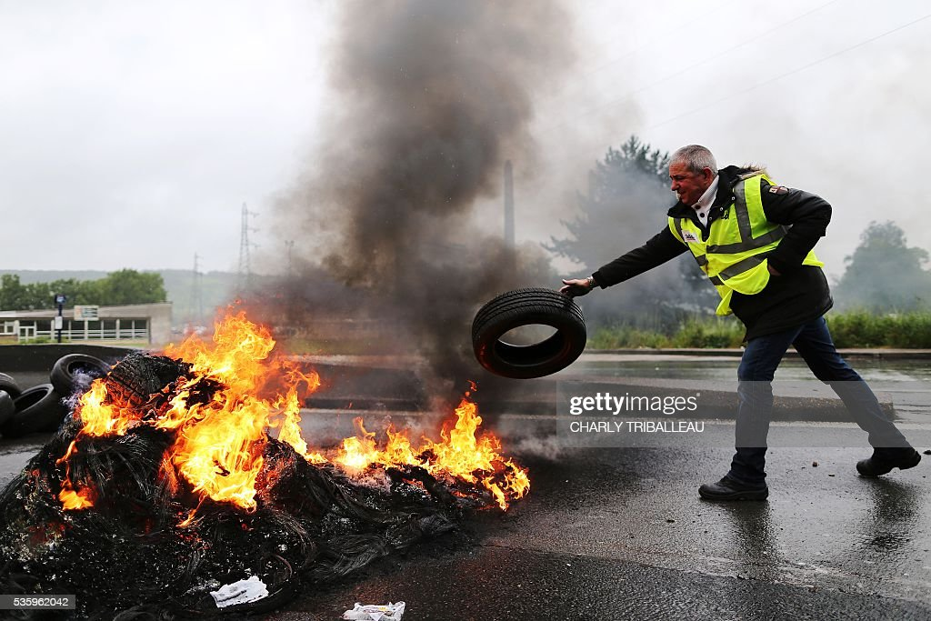 A man puts a tyre on fire as protesters block a road to protest against the government's planned labour law reforms, on May 31, 2016 in Saint-Etienne-du-Rouvray, near Rouen, northwestern France. / AFP / CHARLY