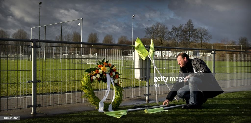 A man puts down corner flags at the memorial site for linesman Richard Nieuwenhuizen at the clubhouse of Dutch football club SC Buitenboys in Almere, on December 9, 2012. Nieuwenhuizen collapsed and fell into a coma after he was attacked by three teenagers at the end of a junior club football match on December 2, 2012. People will gather this afternoon for a silent march in memory of Nieuwenhuizen. AFP PHOTO/ANP/ KOEN VAN WEEL netherlands out