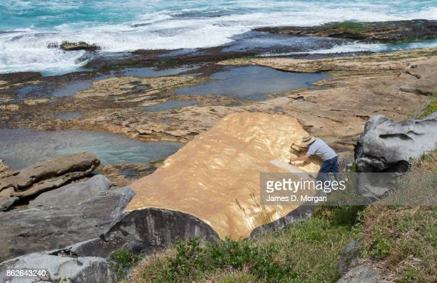 A man puts final touches to 'Klondike' by Karl Chilcott at Sculpture By The Sea on October 18 2017 in Sydney Australia The annual art event draws...