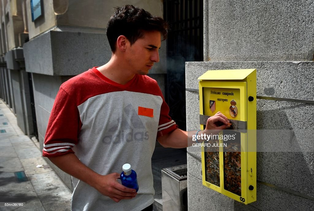 A man puts his cigarette butt in an ashtray displayed by the City Council, and shaped as a ballot box, inviting the passerby to vote with their cigarette butt for the next UEFA Champions League's winner, depicting the logos of both Madrid footbll teams, Atletico de Madrid (L) and Real Madrid, in Madrid on May 26, 2016. Real Madrid and Atletico de Madrid will play the Champions League final football match on May 28, 2016 in Milan. / AFP / GERARD