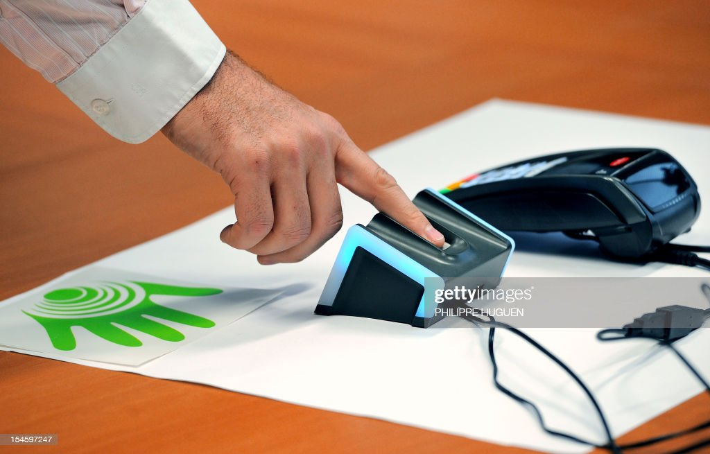 STORY - A man puts his finger on a fingerprint device used for automatic payments on October 18, 2012 at the 'Natural Security' headquarters in Lille, during its presentation. This system, which requires a bank card and a fingerprint registration of its owner at the bank, is to be tested by 1.500 people in Villeneuve-d'Ascq until March 2012.