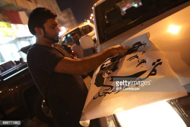A man puts on a car a sticker portraying Qatar's Emir Sheikh Tamim bin Hamad AlThani outside a shop in the capital Doha on June 11 2017 The...