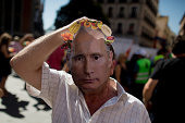 A man puts on a mask depicting Russian President Vladimir Putin wearing a fruit crown during a protest against the Russian food ban giving food away...