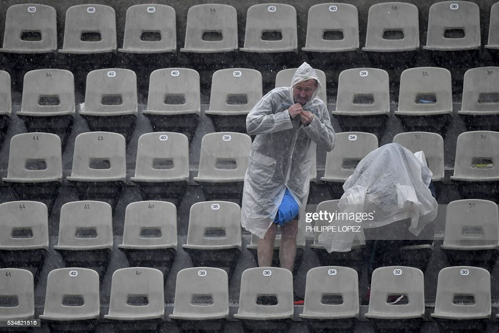 A man puts on a poncho as rain interrupts play during the women's third round match between the US's Venus Williams and France's Alize Cornet at the Roland Garros 2016 French Tennis Open in Paris on May 28, 2016. / AFP / PHILIPPE