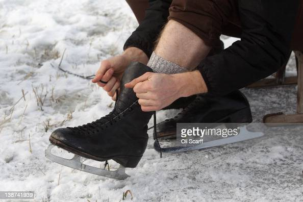 A man puts on his vintage iceskates as he prepares to skate on a frozen fen in subzero temperatures on February 11 2012 in Sutton England Last night...