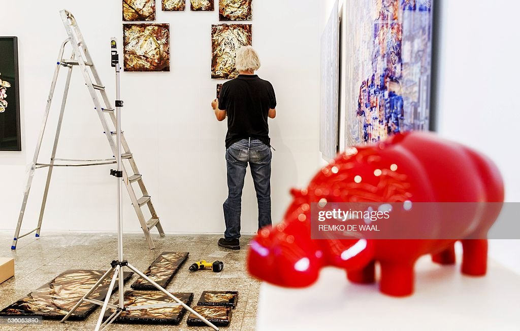 A man puts paintings on a wall during the setting up of the 32nd edition of the KunstRai art fair in Amsterdam, on May 31, 2016. The KunstRai art fair is the longest running art fair for contemporary autonomous and applied art in the Netherlands. / AFP / ANP / Remko de Waal / Netherlands OUT / RESTRICTED