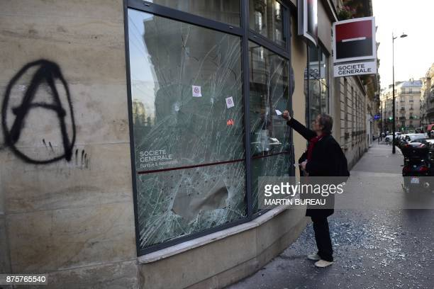 A man puts stickers on the damaged front window of branch of the Societe Generale bank during a march dubbed 'marche sur l'Elysée' called by the...