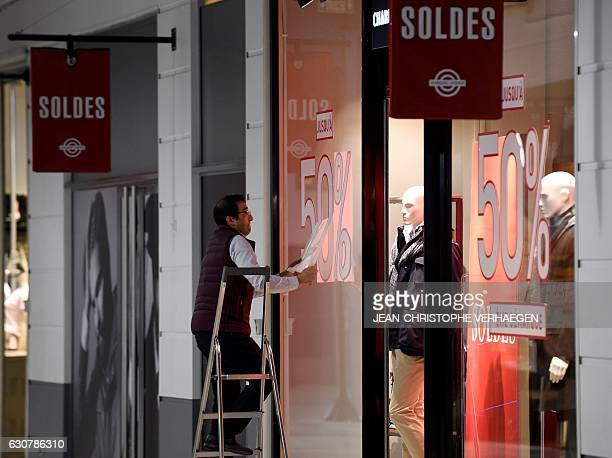 A man puts stickers on the front window of his shop at a mall in Talange eastern France on the first day of the regional winter sales on January 2 a...