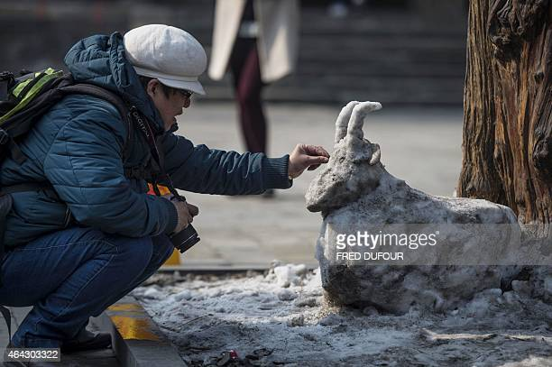 A man puts stones in the eyes of a snow covered goat statue at Dongyue Temple Fair during Chinese Lunar New Year celebrations in Beijing on February...
