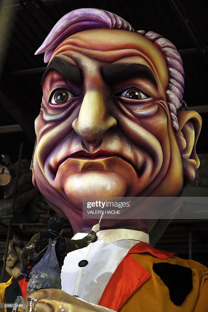 A man puts the final touche on a giant figure of French Dominique Strauss-Kahn on February 8, 2016 in Nice, southeastern France during preparations of the 132st Nice Carnival. The carnival starting from February 13 until 28 February 2016, celebrates this year the 'King of Medias'. / AFP / VALERY HACHE