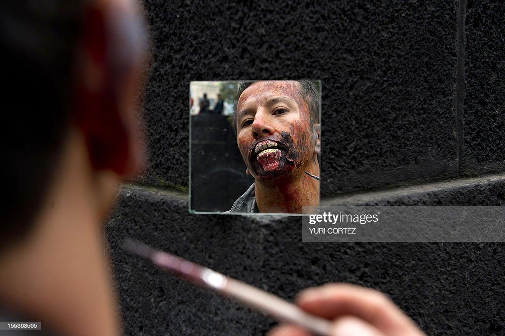 A man puts the final touches to his zombie make up to take part in a 'Zombie Walk' at the Revolution Monument in Mexico City on November 3, 2012. According to the organization, 15,000 people will take part in the event in an attempt to set a new Guinness record. AFP PHOTO/ Yuri CORTEZ