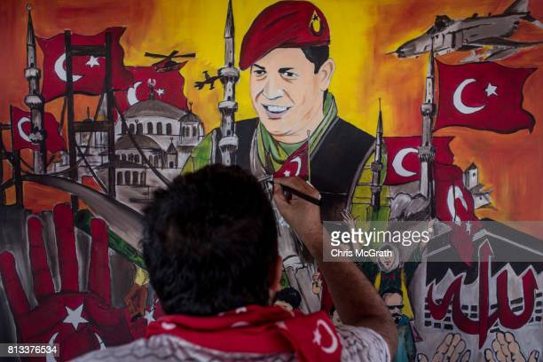 A man puts the finishing touches on a painting depicting the events of the July 15 2016 coup attempt at an anniversary site setup to mark the first...