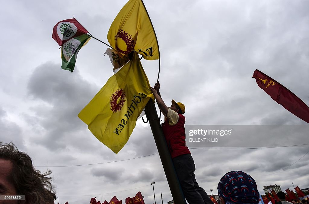 A man puts up flags of the left-wing Education and Science Workers' Union (Egitim-Sen) during a May Day rally in Bakirkoy, a district of Istanbul, on May 1, 2016. Turkish police on clamped down on unauthorised protests during a tense May Day in Istanbul, using tear gas and water cannon against demonstrators and imposing a heavy security blanket on the city. / AFP / BULENT