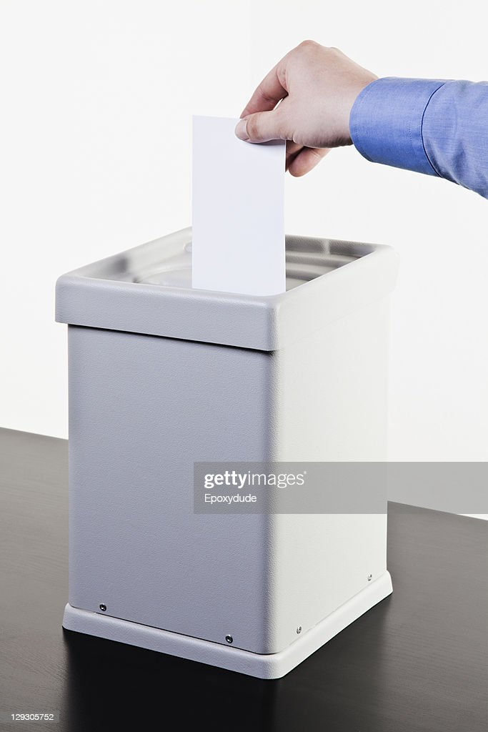 A man putting a blank white ballot into a ballot box, close-up hands : Stock Photo