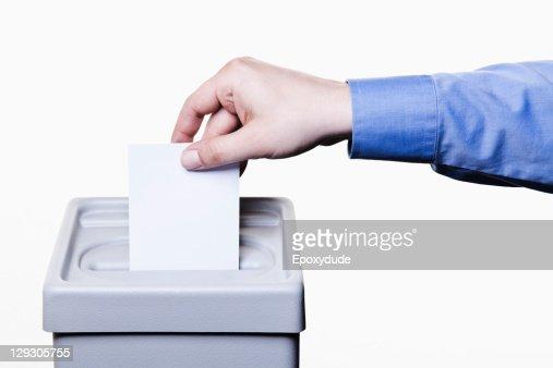 A man putting a blank white ballot into a ballot box, close-up hands