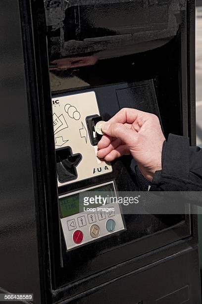 A man putting a coin into a car park meter
